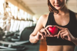 Happy sport woman holding red heart